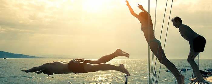 Ungdomar dyker från båt i solnedgången