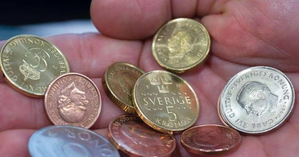 hand med svenska mynt