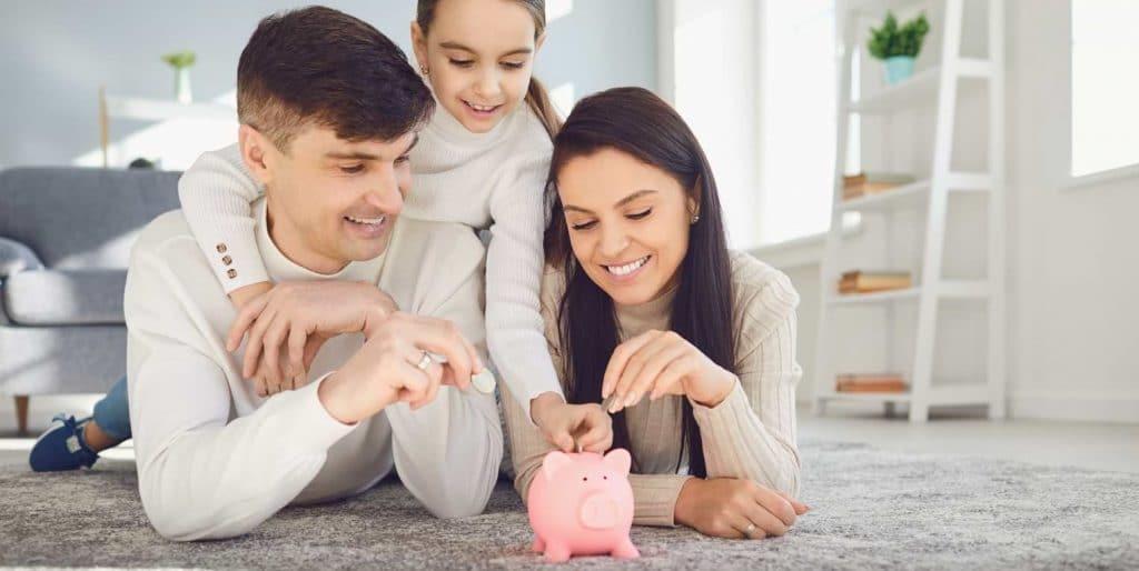 Familj som lägger pengar i spargris