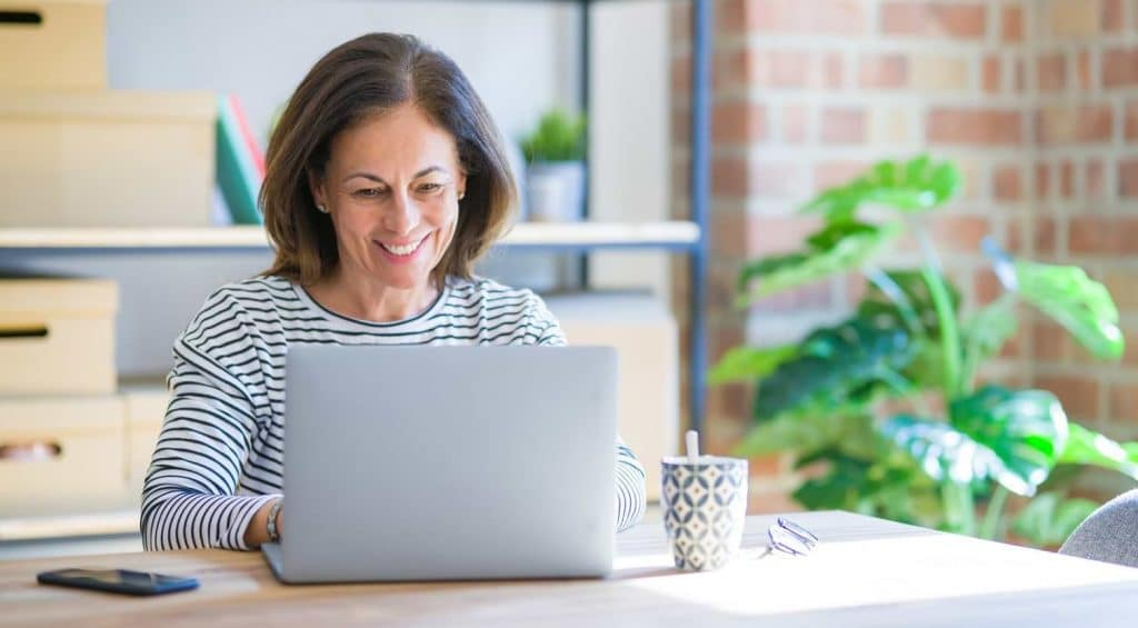 Kvinna som investerar sina pengar via dator