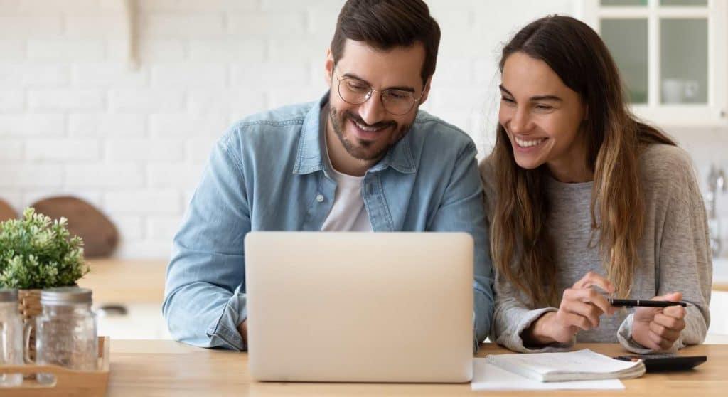 Man och kvinna vid dator som investerar sparpengar