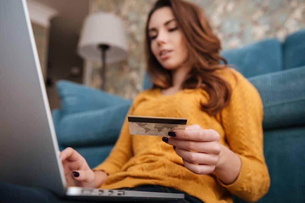 Kvinna vid dator med kreditkort som e-handlar