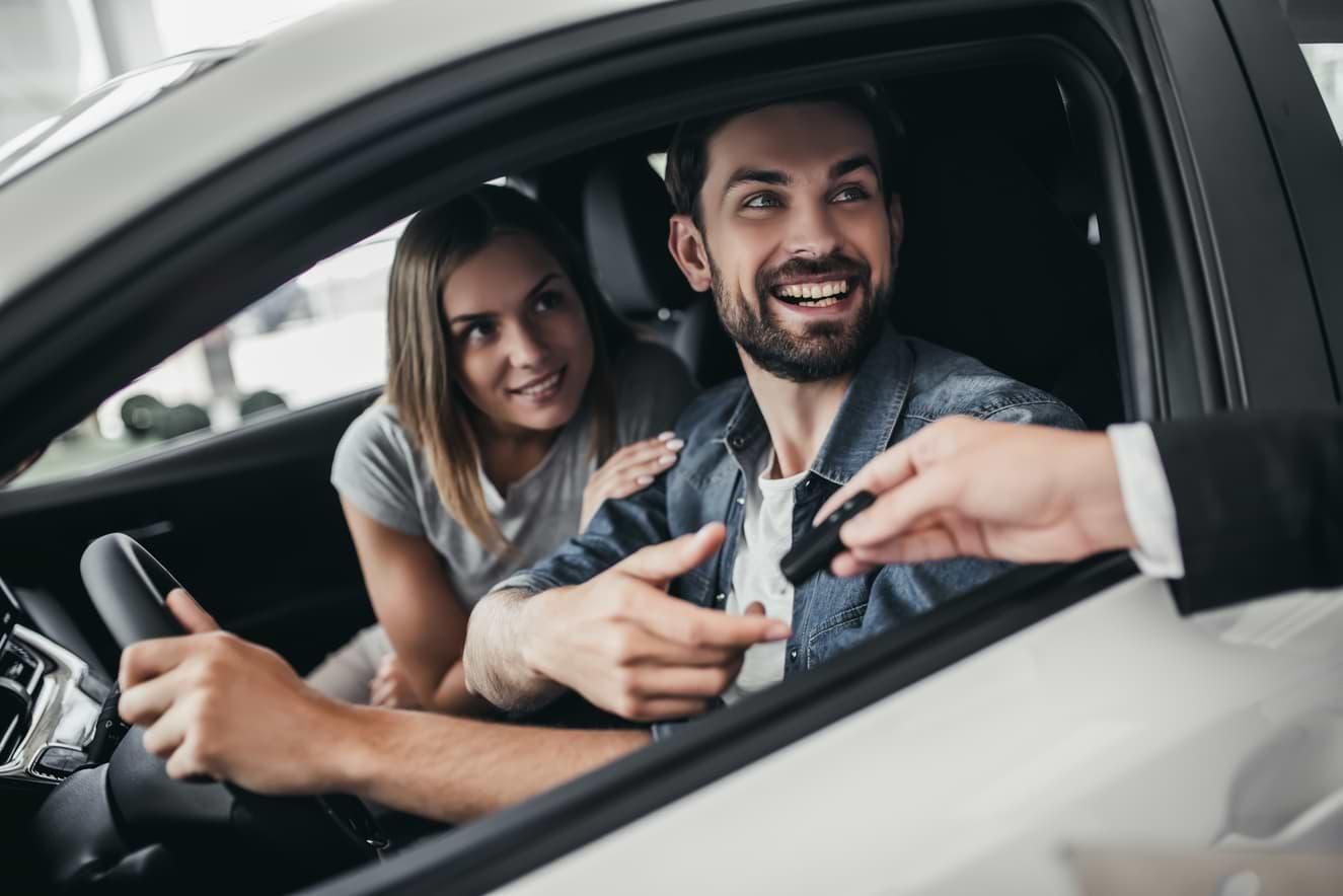 Man och kvinna i ny bil som ges nycklarna