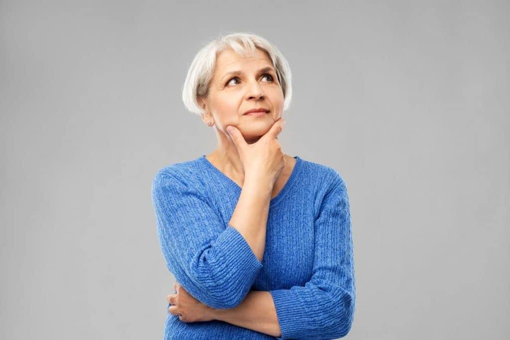 Fundersam äldre kvinna i blå tröja