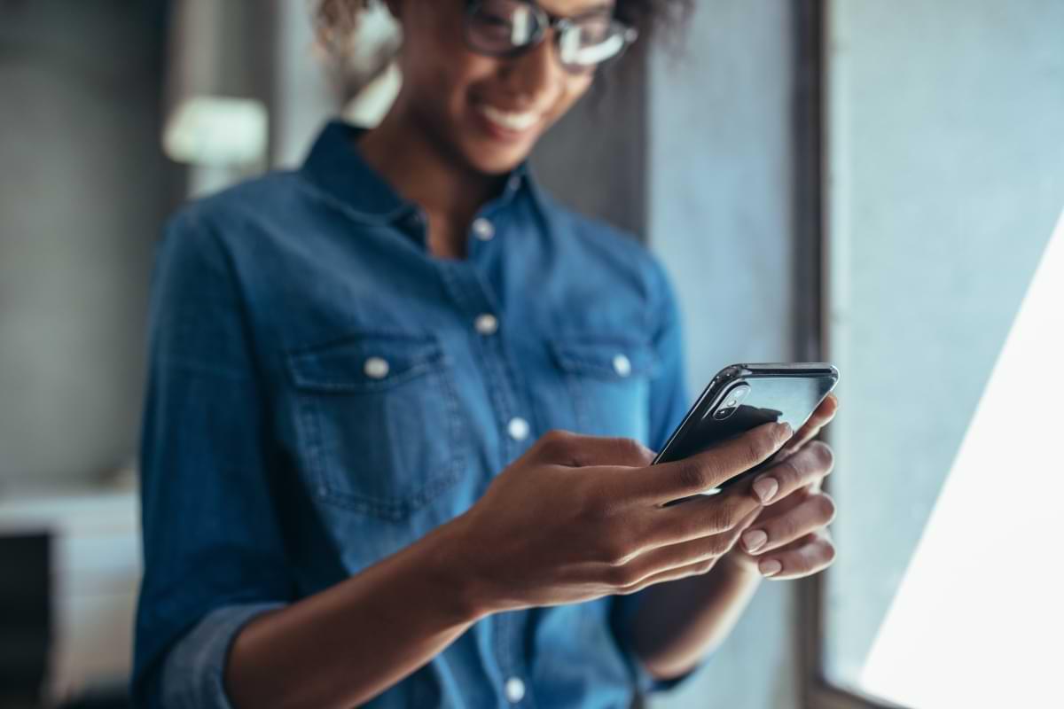 Leende kvinna med mobil i handen