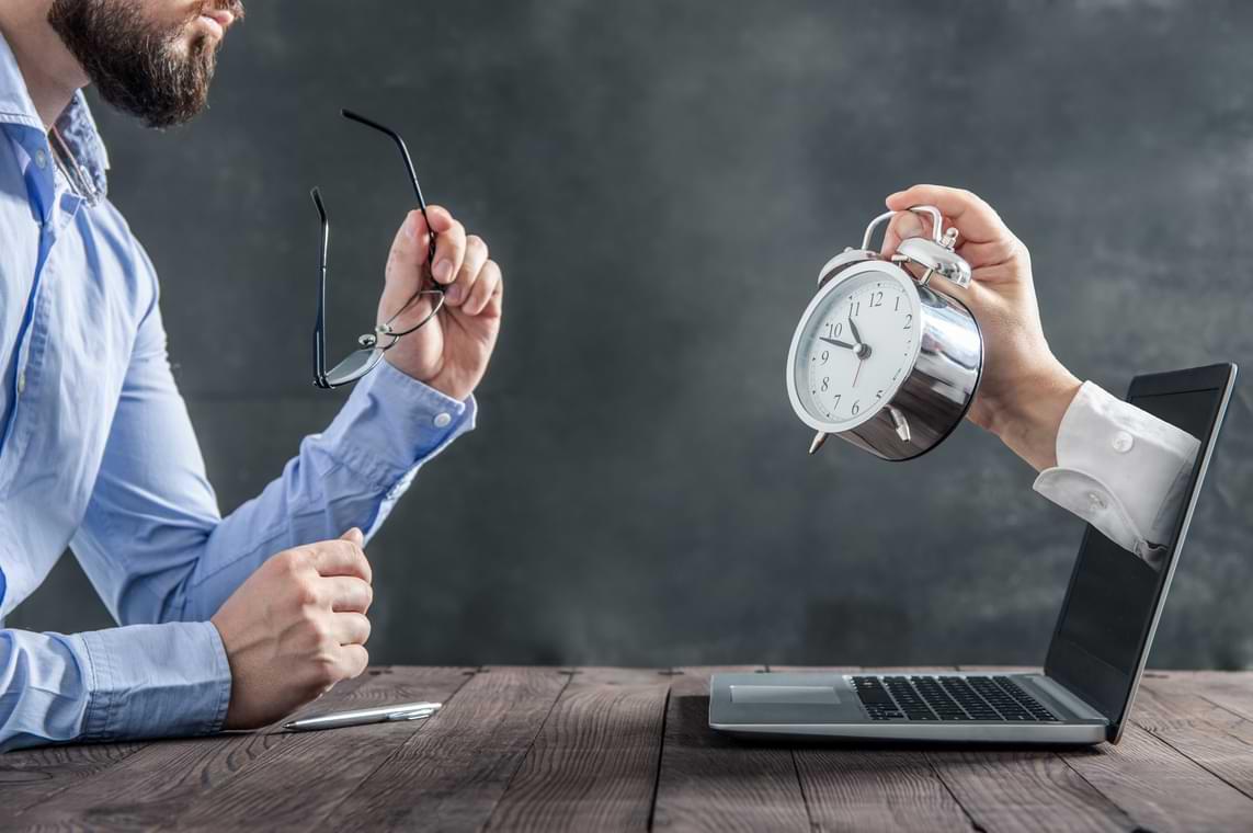 Stressad man vid dator med klocka