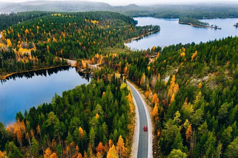 Lång väg i skogen med röd bil