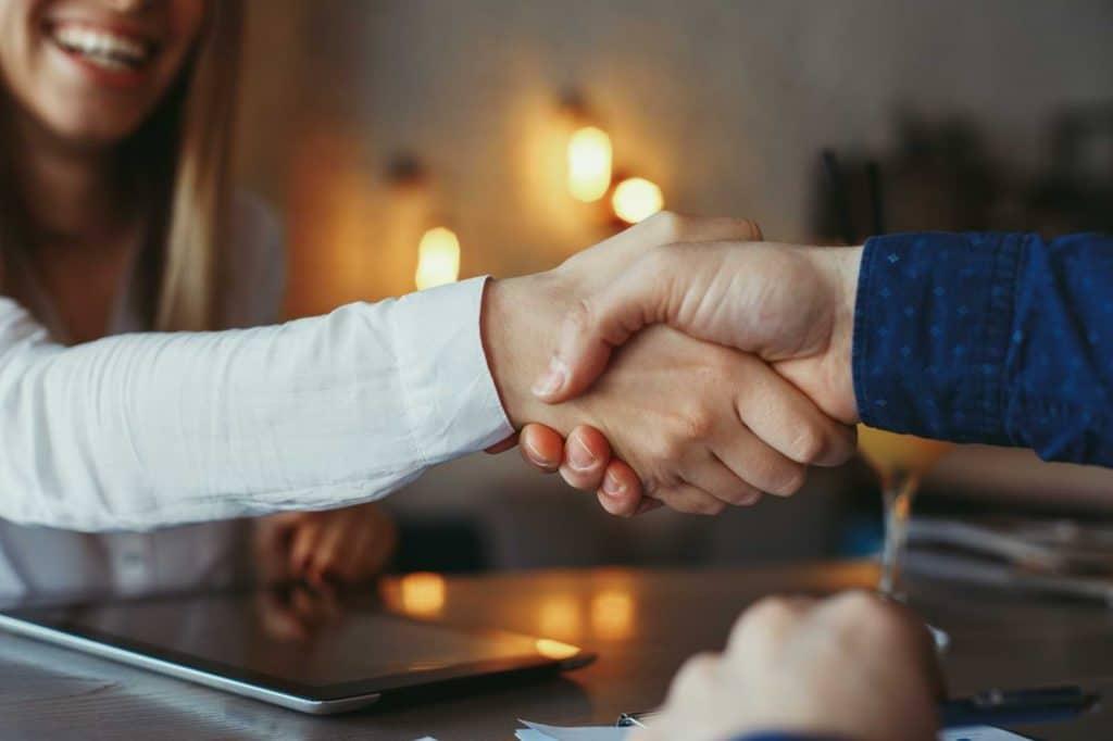 Kvinna och man skakar hand