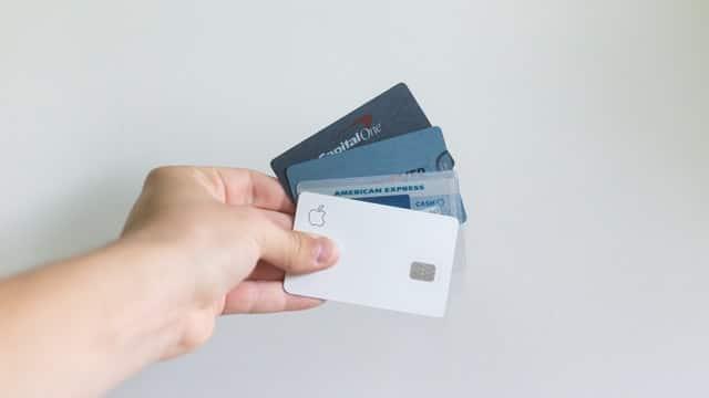 En hand som håller i en mängd kreditkort.