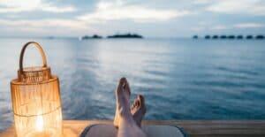 En person som ligger och njuter nere vid havet på sin semester.