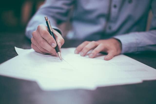 En man som skriver under en mängd dokument.