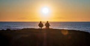 Ett par som sitter och tittar på solnedgången.