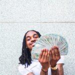 En man som håller i en stor bunt med amerikanska 100-dollarsedlar.