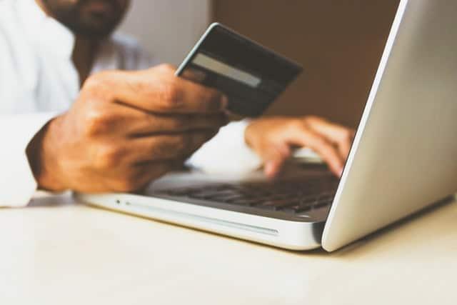 En person som sitter framför en laptop med ett kreditkort i ena handen.